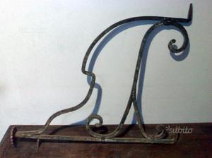 Due elementi in ferro battuto usati come appendi
