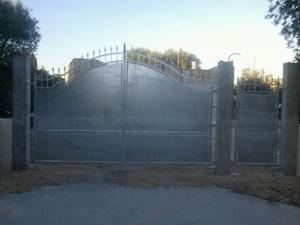 Cancello in ferro battuto chiuso con pannelli in lamiera