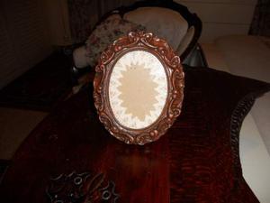 Cornice ovale in legno di noce intagliato