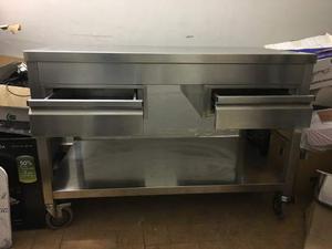 Un tavolo in acciaio a 2 piani con ruote e 2 cassetti