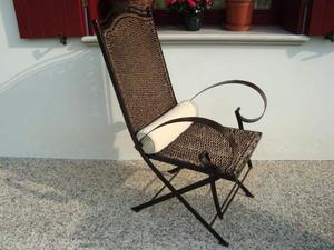 Sedia in ferro battuto e paglia intrecciata.