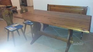 Tavolo in legno con panca angolare e sedie