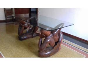 Tavolo in cristallo con alla base due statue di legno