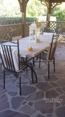 Tavolo in travertino e sedie in ferro battuto