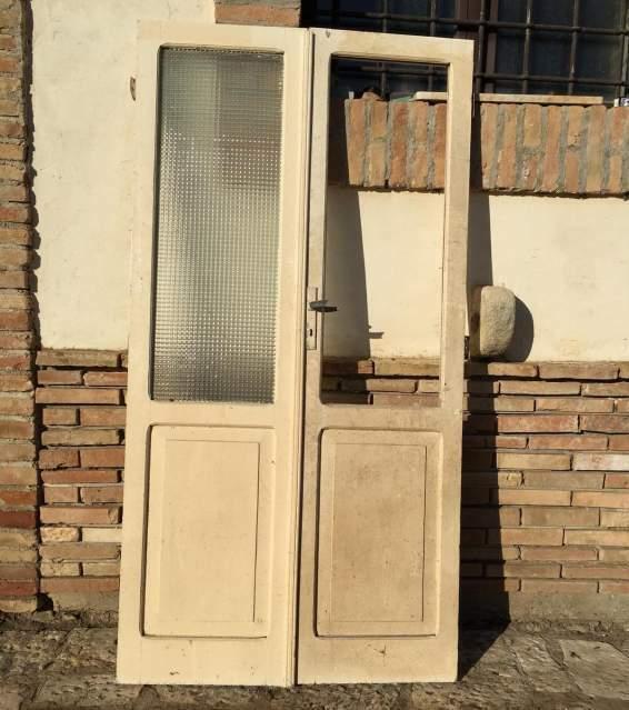 Antica porta in legno massello a due ante vetrata bugnata