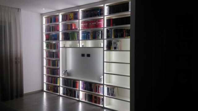 Libreria in nicchia con porta tv e ripiani a giorno