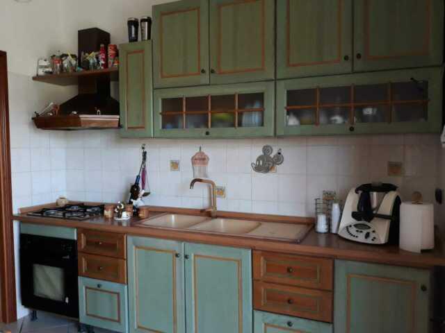 Cucina in legno completa di tavolo e sedie